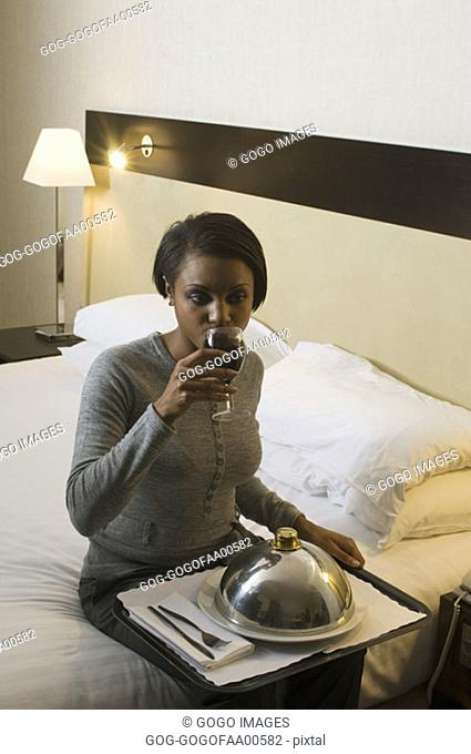 Businesswoman eating a room service dinner