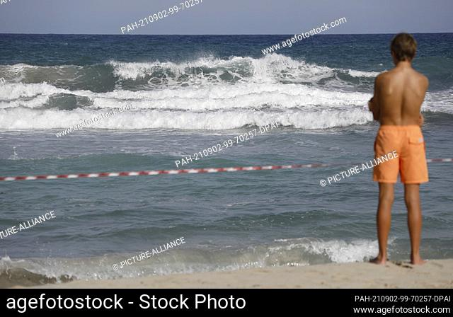 02 September 2021, Spain, Manacor: A man stands on the closed off beach of Cala Mendia in Manacor on Mallorca. Two young holidaymakers from North...