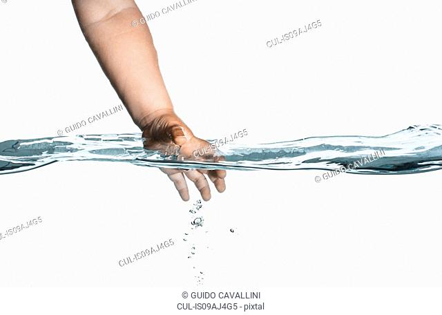 Surface level view of toddlers hand reaching into clear water