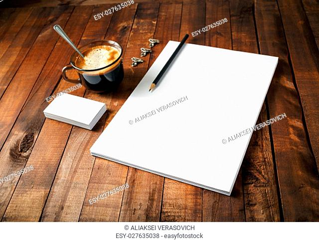 Blank paperwork template with plenty of copy space on vintage wooden table background. Mockup for branding identity. Blank objects for placing your design