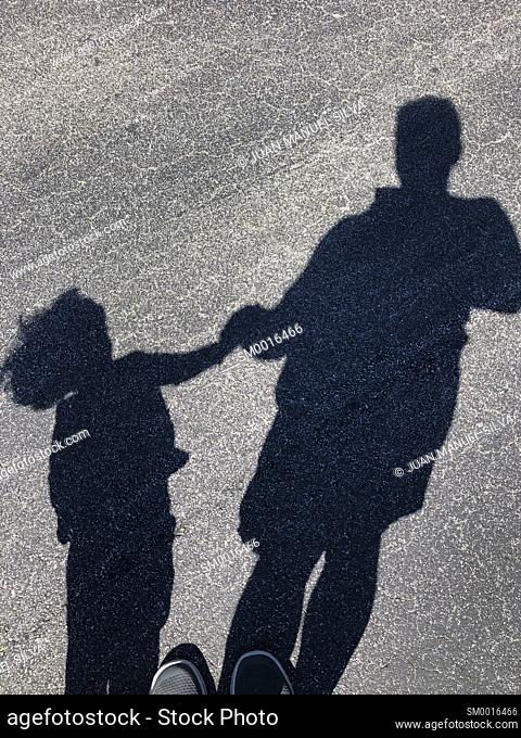 Shadow of man with child in the street