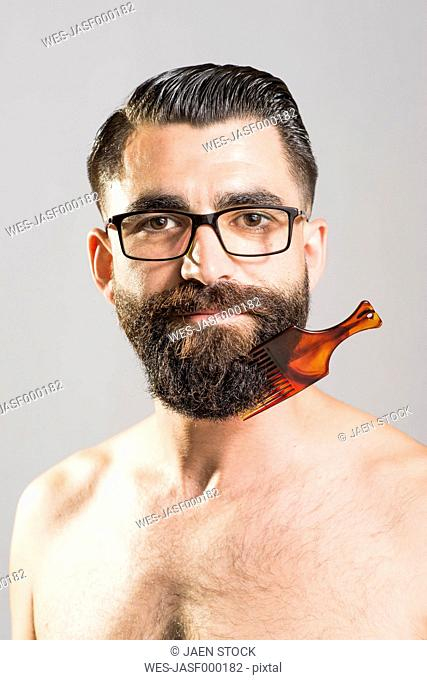 Bare-chested man with glasses and comb stuck in beard