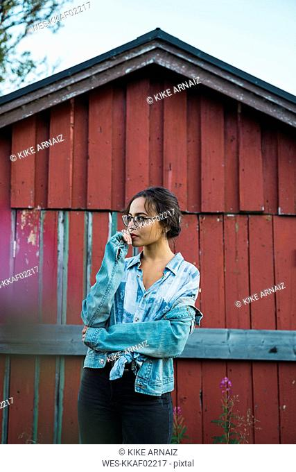 Portrait of a young woman standing in front of a red wood hut