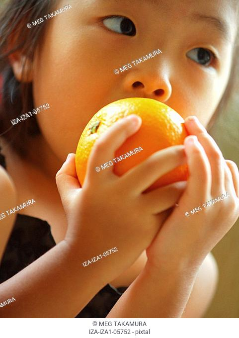 Portrait of a girl biting an orange