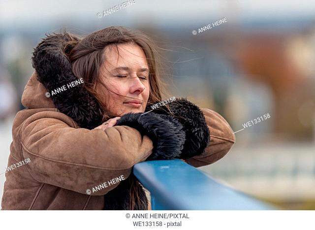 Woman waiting on bridge looking into distance, leaning head on hand,bridge,Bonn,Germany