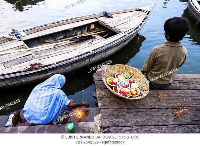 Old lady and child lighting puja candles by Ganges river, Varanasi, India