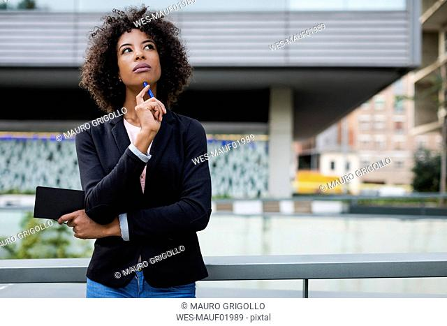 Portrait of thinking businesswoman with notebook and pen outdoors