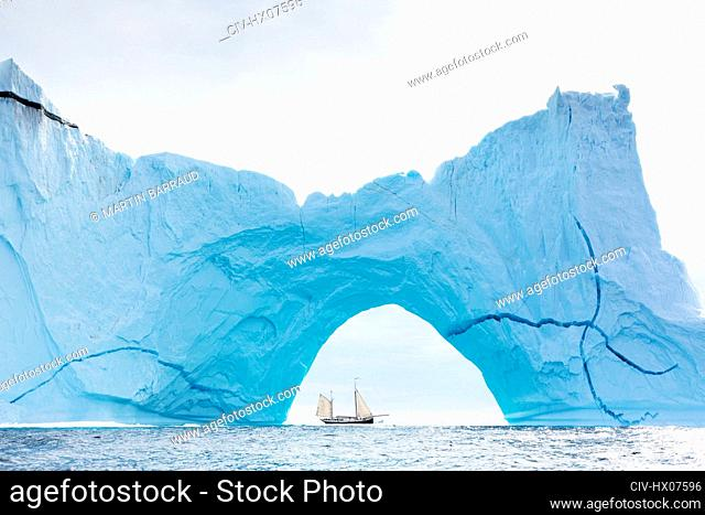 Ship sailing behind majestic iceberg arch on Atlantic Ocean Greenland