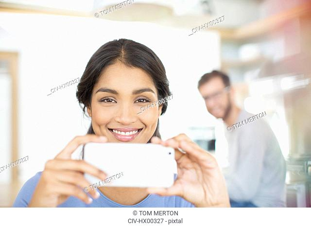 Portrait smiling woman using camera phone