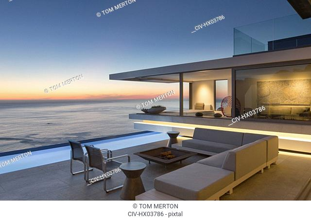 Illuminated modern, luxury home showcase exterior patio with sofa and lap pool with ocean view at dusk