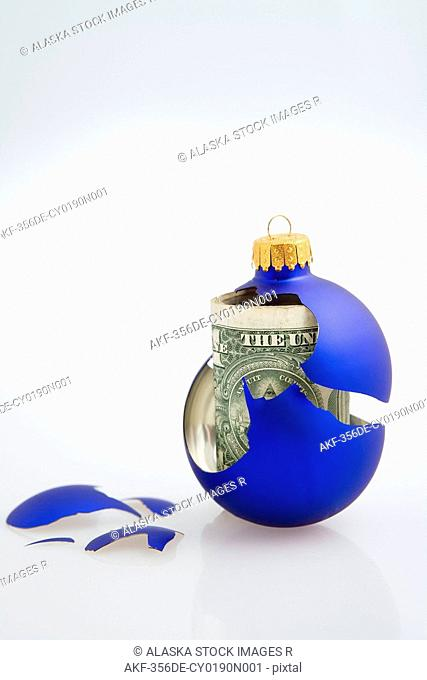 Closeup of one blue Christmas tree bulb ornament broken with dollar bill inside on white background studio portrait