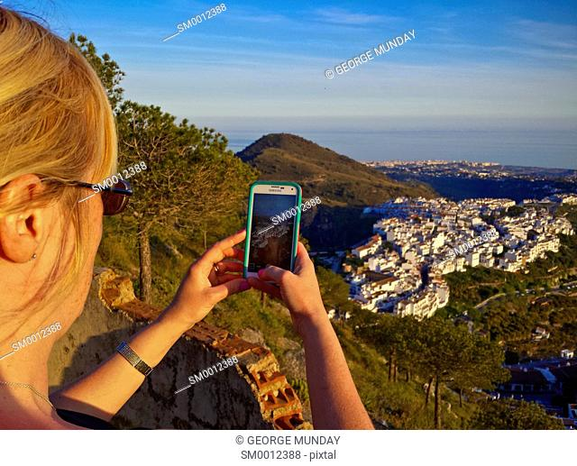 Woman photographing the newly developed part of Frigiliana