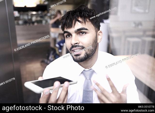 Businessman in cafe, explaining idea on phone