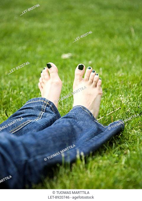 A woman lying in a park has black nail polish on her toe nails