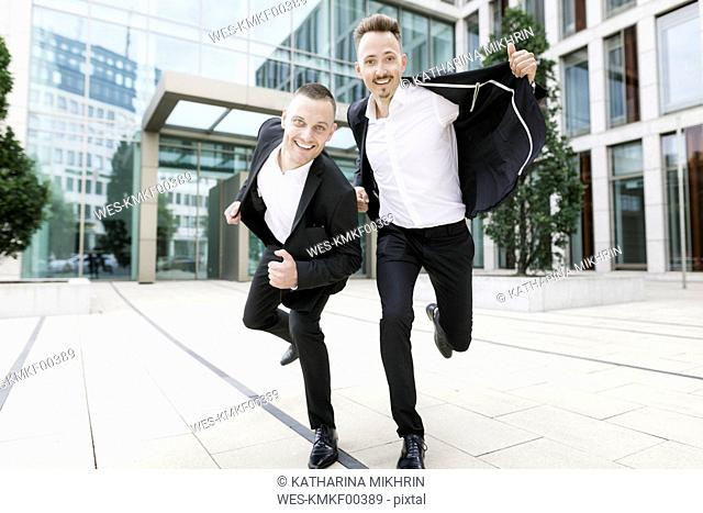 Two happy businessmen in front of office building