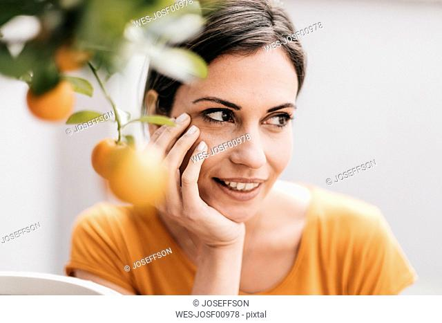 Woman relaxing next to orange tree