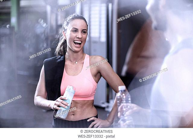 Woman laughing with friend at gym
