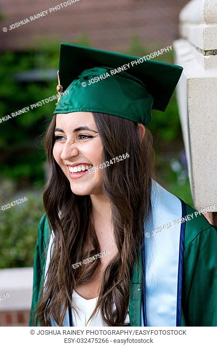 Pretty girl posing for a graduation photo on campus during her senior year of college right before graduation