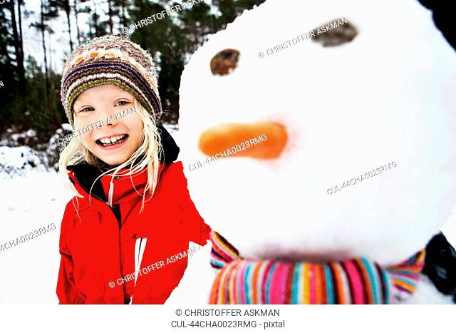 Smiling girl with snowman in meadow