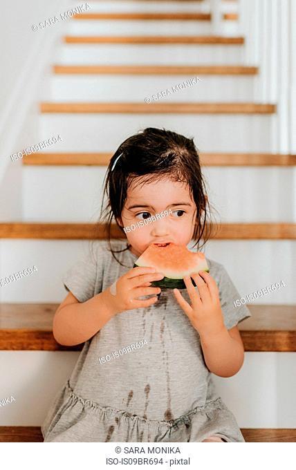 Girl enjoying watermelon on stairs