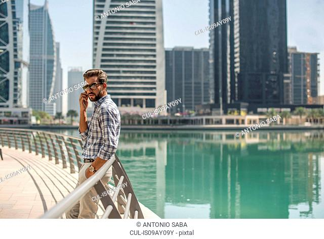 Young man leaning against waterfront railings talking on smartphone, Dubai, United Arab Emirates
