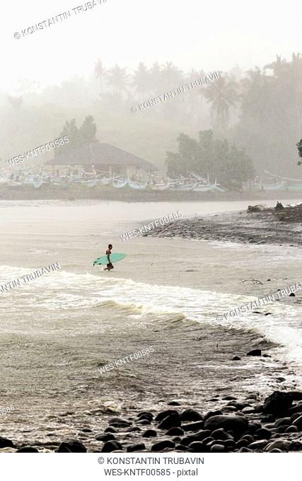 Indonesia, Bali, surfer carrying surfboards in the sea