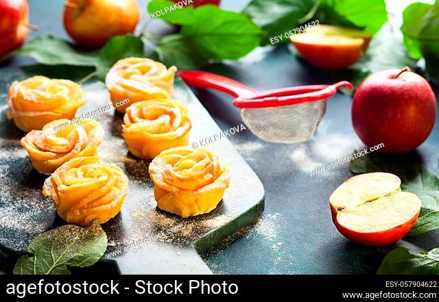 Apple Rose mini tarts with icing sugar on the stone cutting board