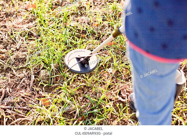 Cropped view of girl using metal detector in field