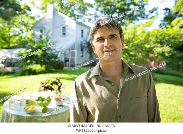 Outdoors in summer. On the farm. A man in a farmhouse garden, beside a round table with fresh lemonade drinks