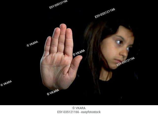 Children violence. Girl with her hand extended signaling to stop