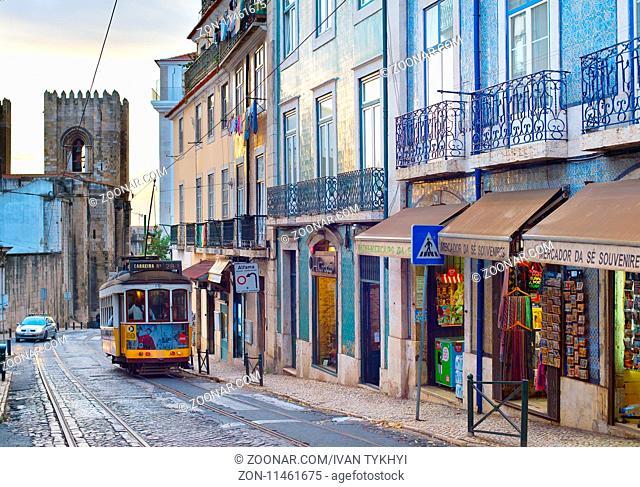 LISBON, PORTUGAL - DEC 07, 2016: Tram 28 on Alfama street. Alfama district is the Old Town of Lisbon, famous tourist attraction