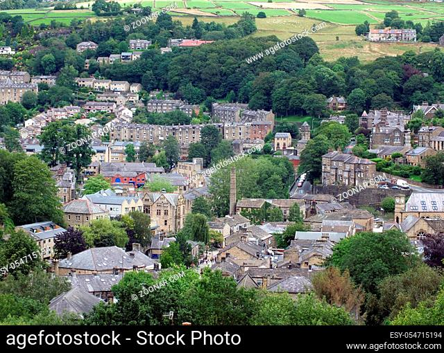 an aerial view of the town of hebden bridge with streets and houses surrounded by summer trees and fields
