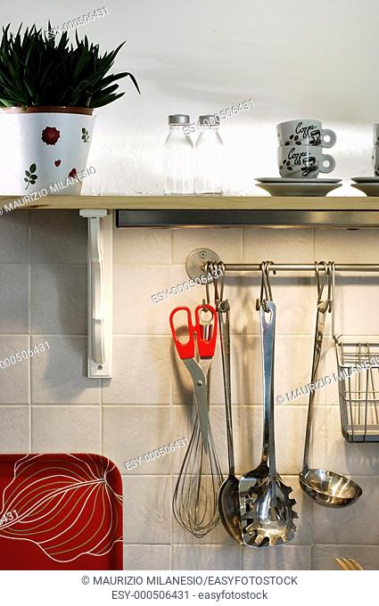 Kitchen utensils hanging on the wall and cup and salt shaker on the shelf