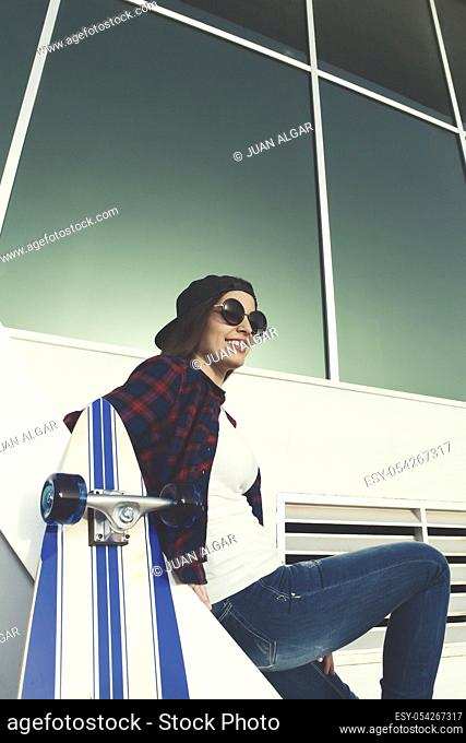 Shot of smiling female in sunglasses sitting on stairs near skate