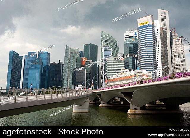 Singapore, Republic of Singapore, Asia - Cityscape with dark thundery clouds over the skyline and the skyscrapers of the central business district at Marina Bay