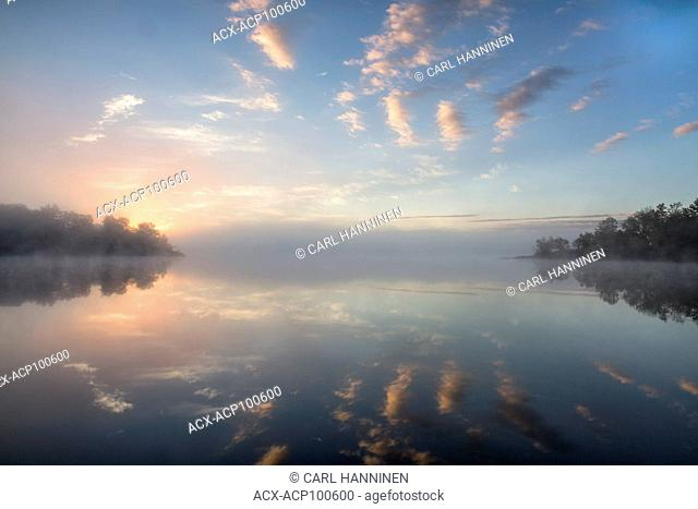 Morning sun creeping over horizon on foggy morning, Vermilion River, Whitefish, Ontario, Canada