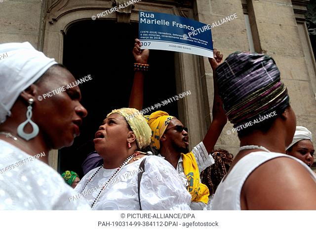 """14 March 2019, Brazil, Rio de Janeiro: """"""""Marielle Franco Street"""""""", stands on the banner of a man in front of a church where a service was held in honour of the..."""
