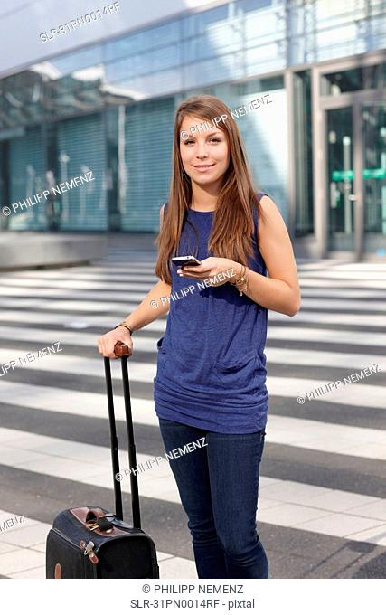 Woman with cellphone and suitcase