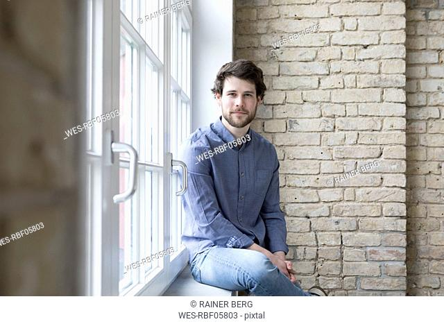 Young businessman sitting on window sill