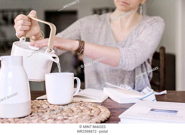 Woman sitting at a table in her apartment, pouring hot water into a mug, morning routine