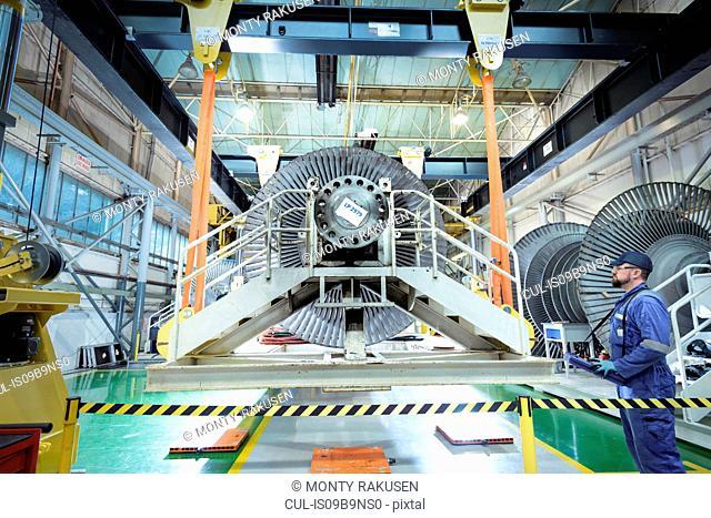 Engineer operating crane in turbine maintenance factory