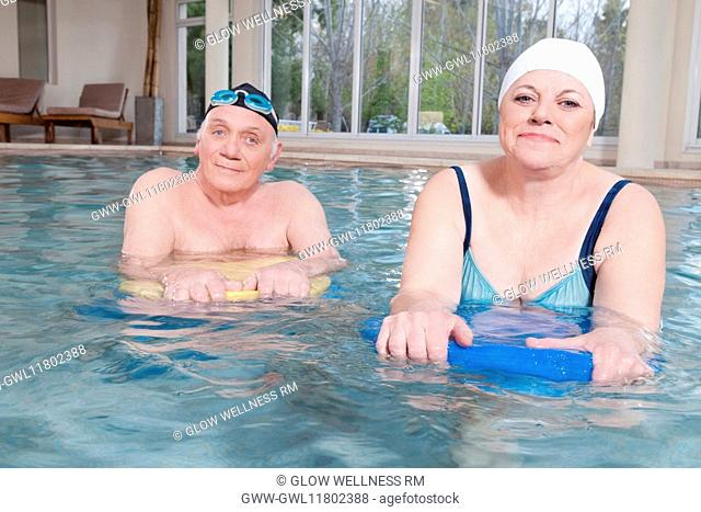 Portrait of a couple swimming with floats in a swimming pool