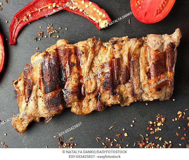 grilled pork ribs on a black board, fresh red tomatoes and chili peppers, top view