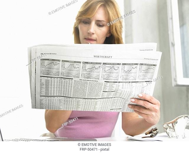 Business woman is reading the newspaper