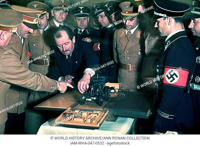 Colour photograph of the automobile engineer and designer Ferdinand Porsche (1875-1951) presents Adolf Hitler (1889-1945) with a model car during celebrations...