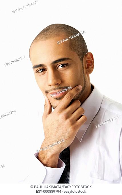 Torso of a handsome African Hispanic business man in white shirt and gray tie with hand on chin and thinking, isolated