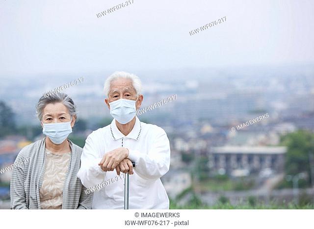 Japan, Tokyo Prefecture, Senior couple wearing flu mask, portrait