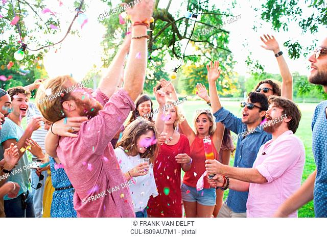 Adult crowd celebrating with arms raised at sunset party in park