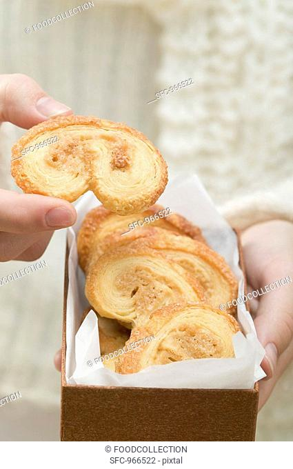 Hand taking palmier puff pastry biscuit from box