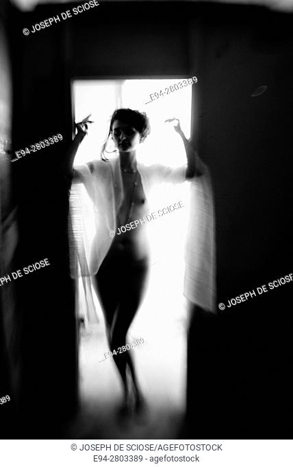 A nude and silhouetted young woman standing in a door way with her arms raised, black and white